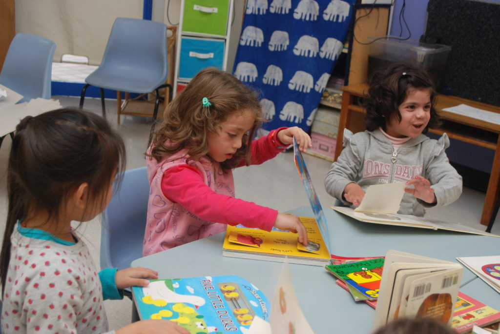 Preschool girls sitting at a table reading picture books